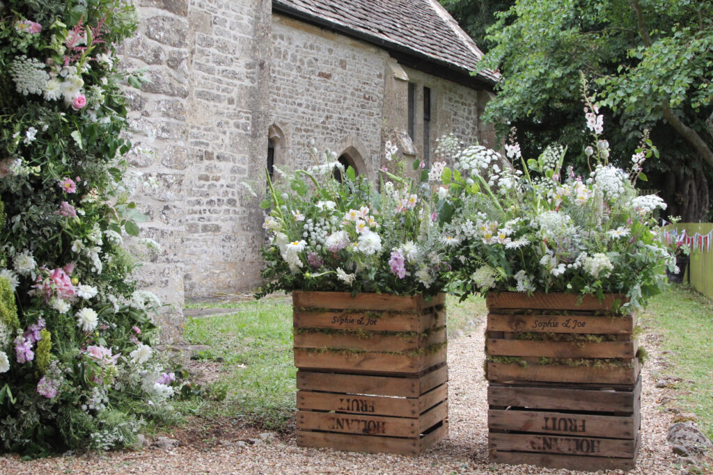 Beautiful meadow style flower crates filled with summer flowers welcome wedding guests to the church. My Flower Patch