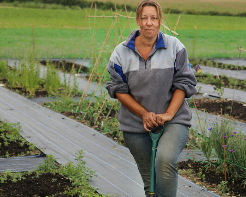 Debbie of Nature's Posy stands with her digging fork on her cut flower farm, preparing the soil for her seedlings.