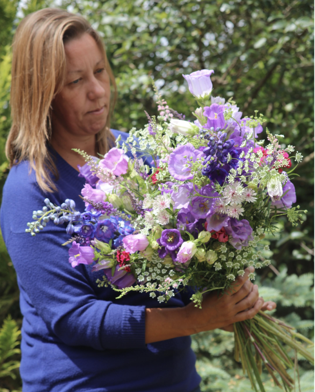 Debbie of Nature's Posy, Cambridgshire, holds an abundant meadow style bouquet filled with freshly cut British flowers from her flower farm. It's filled with the pretty purples of Canterbury Bells,starry pale pink astrantia, frothy white ammi majus and the stately blue spires of delphiniums.