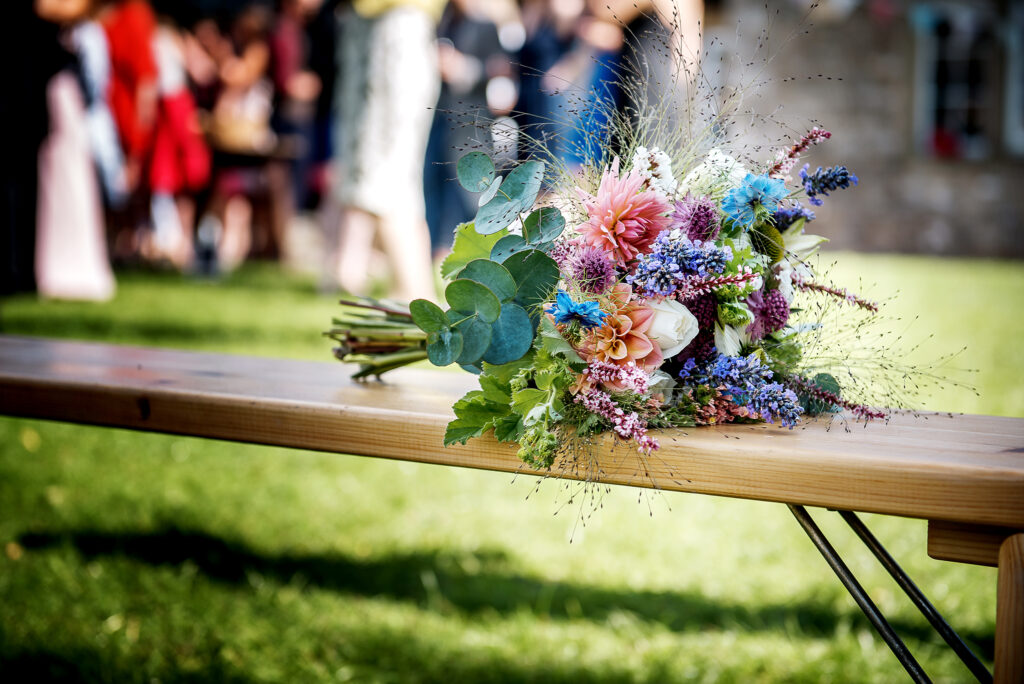 A seasonal summer wedding bouquet of British flowers by Pear Tree House Flowers. Peach dahlias with love in a mist for something blue, lavender for gorgeous perfume, grasses and eucalyptus for texture. Photo: RD Photography.