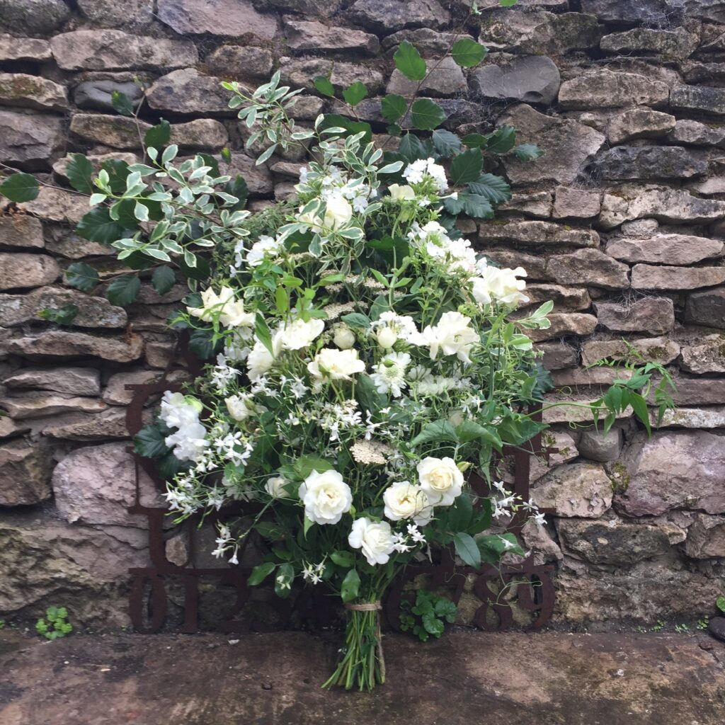 A white summer sheaf by Picking Posies leans against a dry stone wall.