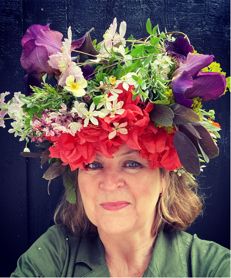 Queenie's Floral Design owner, Gretel Cooper wears an exuberant bright flower crown with red acer leaves, foliage and purple flowers.