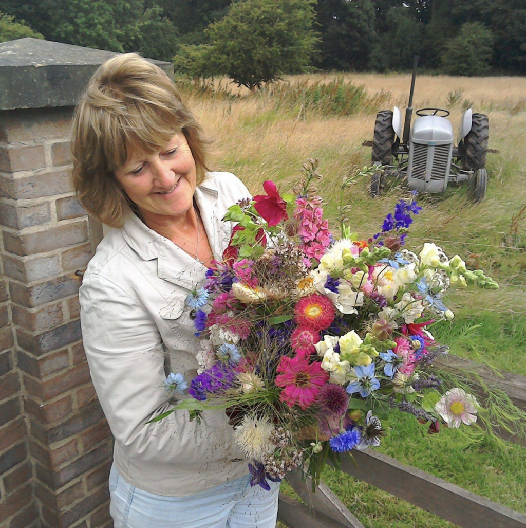 Sandra Bright of Peacock Cottage Flowers holds a colourful bouquet of British cut flowers