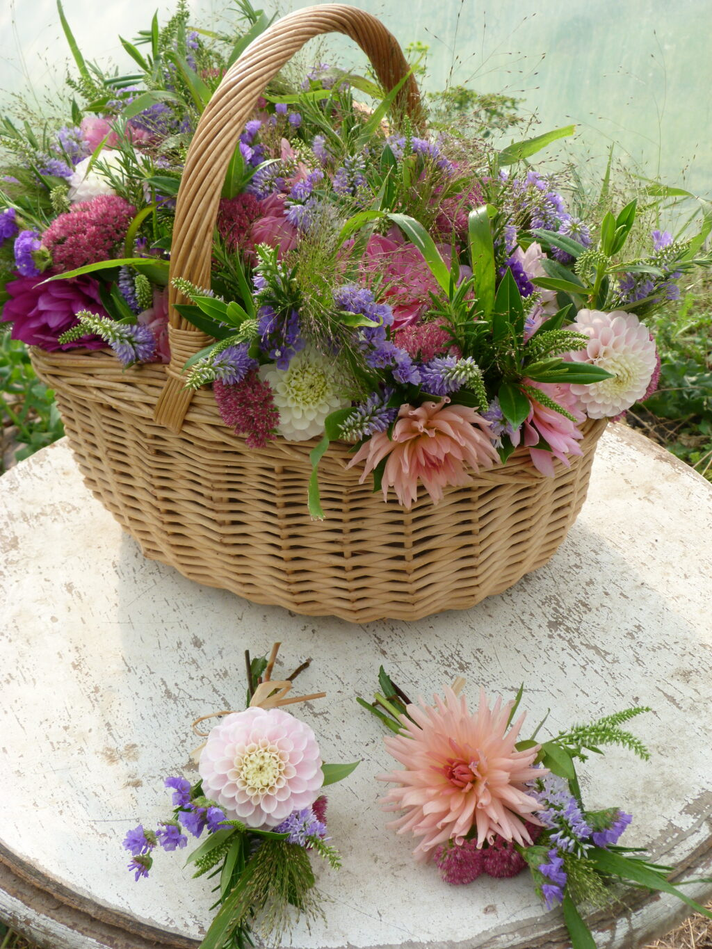 A rattan basket filled with summer flowers for a funeral by The Sussex Cutting Garden.