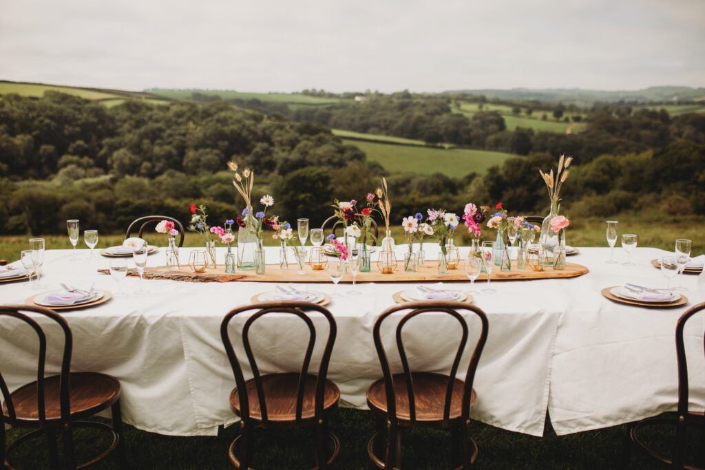 A botanical wedding table by Sweet Peas and Sunflowers photographed against the Devon countryside by Holly Collings Photography.