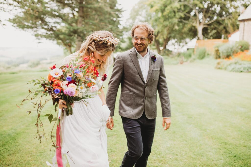 A colourful summer wedding bouquet is carried by the bride as she walks through the garden with her new husband. Flowers by Sweet Peas and Sunflowers. Photo: Holly Collings Photography.