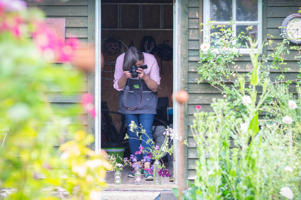 Her business allows Carole to combine her love of growing, flowers and photography. Here she's taking photos of arrangements on her workshop doorstep.