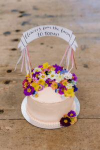A 10th birthday cake for Flowers from the Farm, decorated with edible flowers by Tallulah Rose Flower School. The edible flowers are primulas from Maddocks Organics.