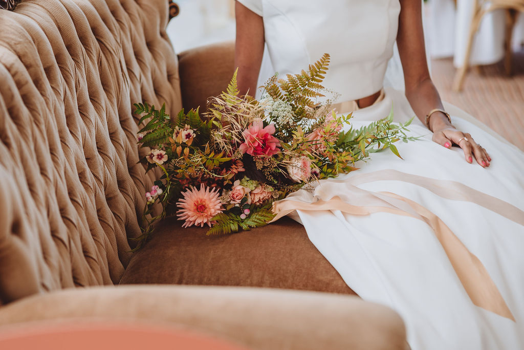 A bouquet of autumn dahlias rests on a button back sofa. Flowers by the Flower Patch. Photo by Megan Wilson Photography.