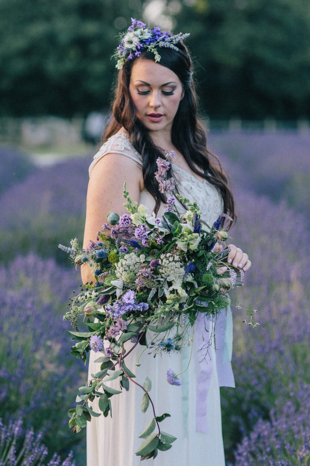 A beautiful cascading bouquet of lilac flowers captured as a bride holds it in a lavender field.