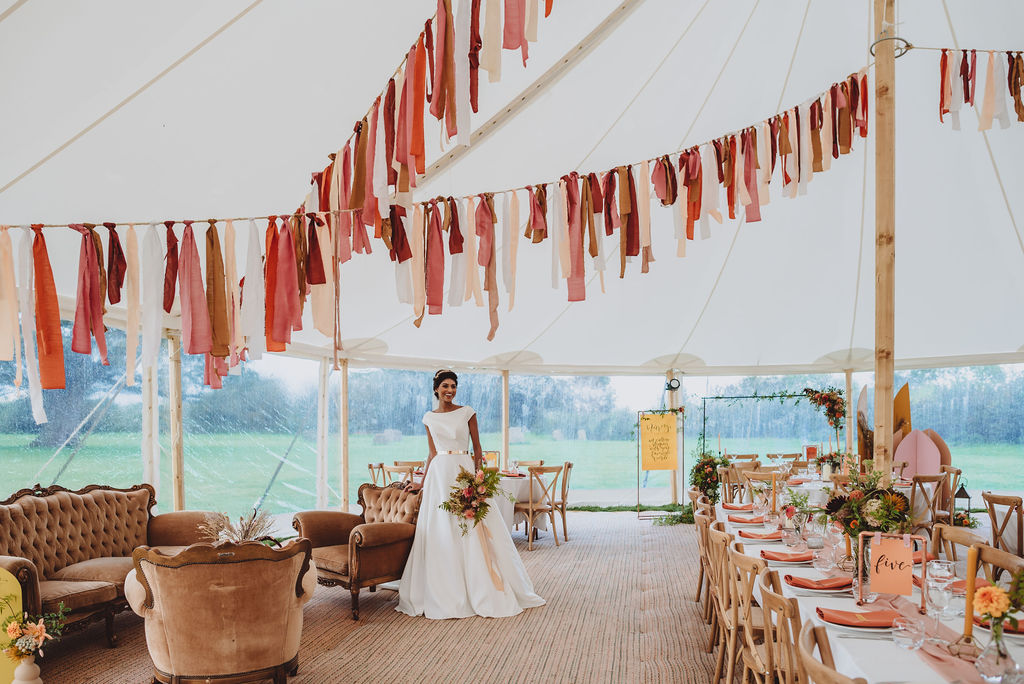 A bride stands with her late summer bouquet in a tipi wedding decorated with bunting overhead and dahlias on the long trestle tables for guests