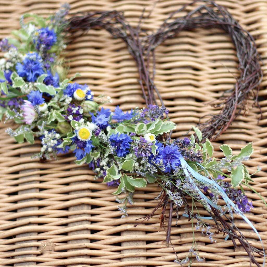 A heart wreath for a funeral decorated with cornflowers by Tuckshop Flowers