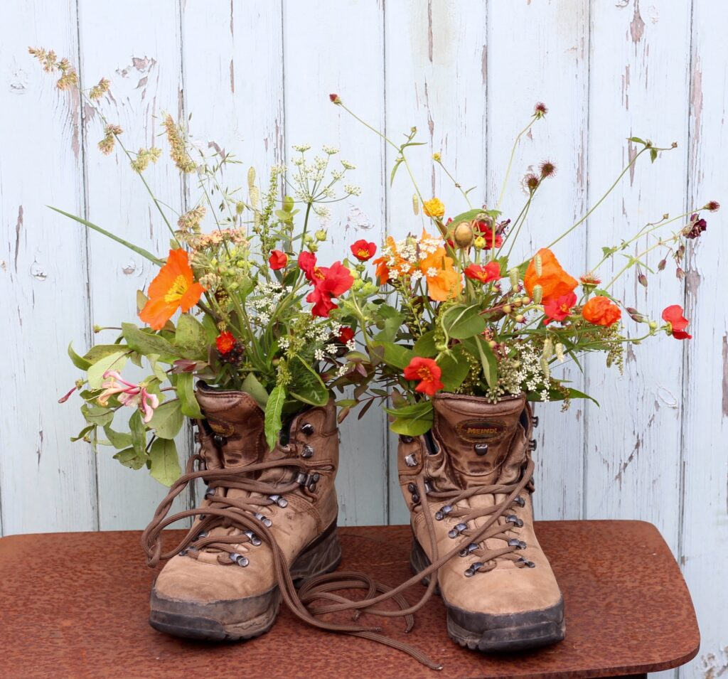 Hiking boots filled with vibrant and wild early summer flowers in shades of orange by Tuckshop Flowers, Birmingham