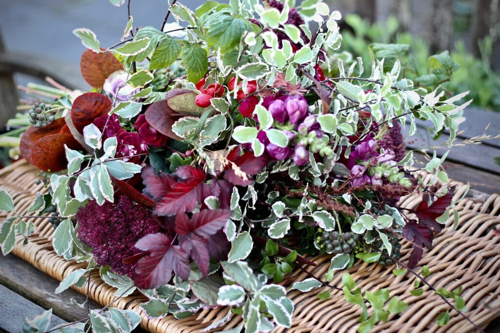 A foliage inspired funeral sheaf with Burgundy physocarpus, variegated pittosporum and ivy is full of texture and colour. Tuckshop Flowers