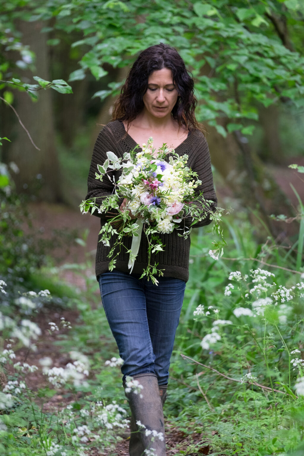 Emma de Sousa, Urban Flower Farmer walks along a grassy path, surrounded by hedges and greenery, holding a seasonal wedding bouquet of flowers she has grown in her cutting garden. Photo: Emma Davies Photography.
