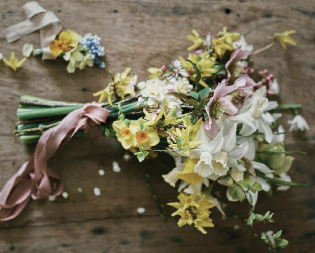 A soft romantic bouquet of yellow and white narcissi with touches of pink from speckled hellebore blooms and silk ribbon.