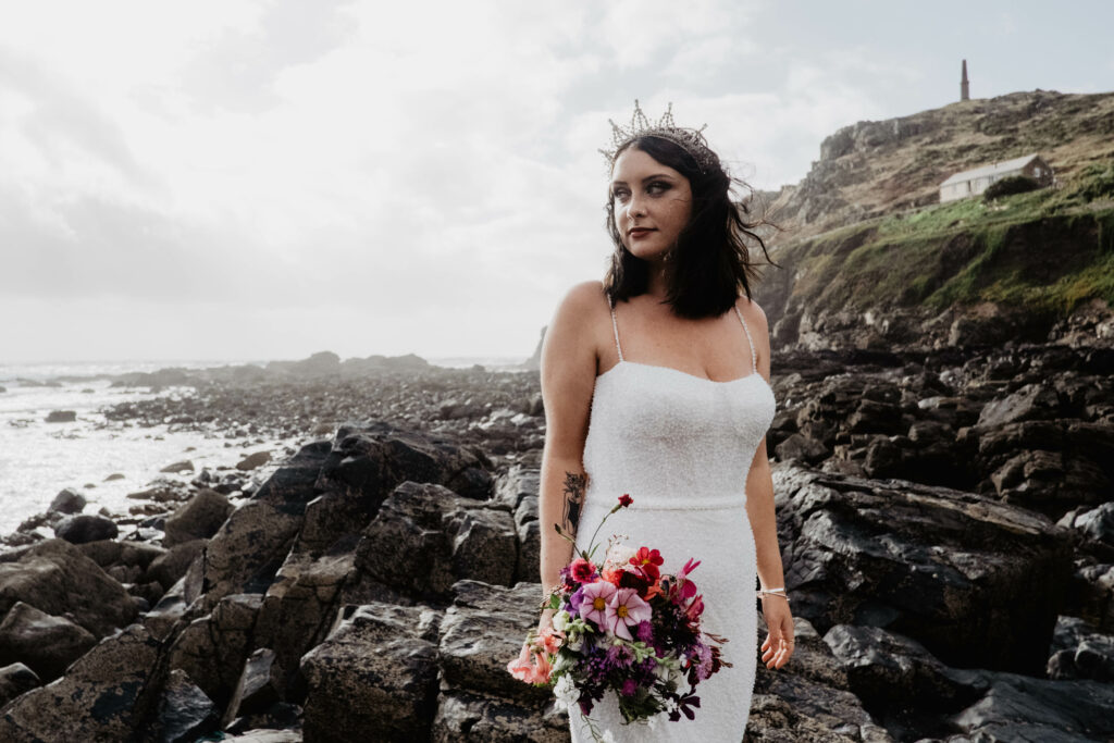 A seaside bride holds a bouquet of summer flowers standing next to rock pools on a Cornish beach. Wild West Flowers.