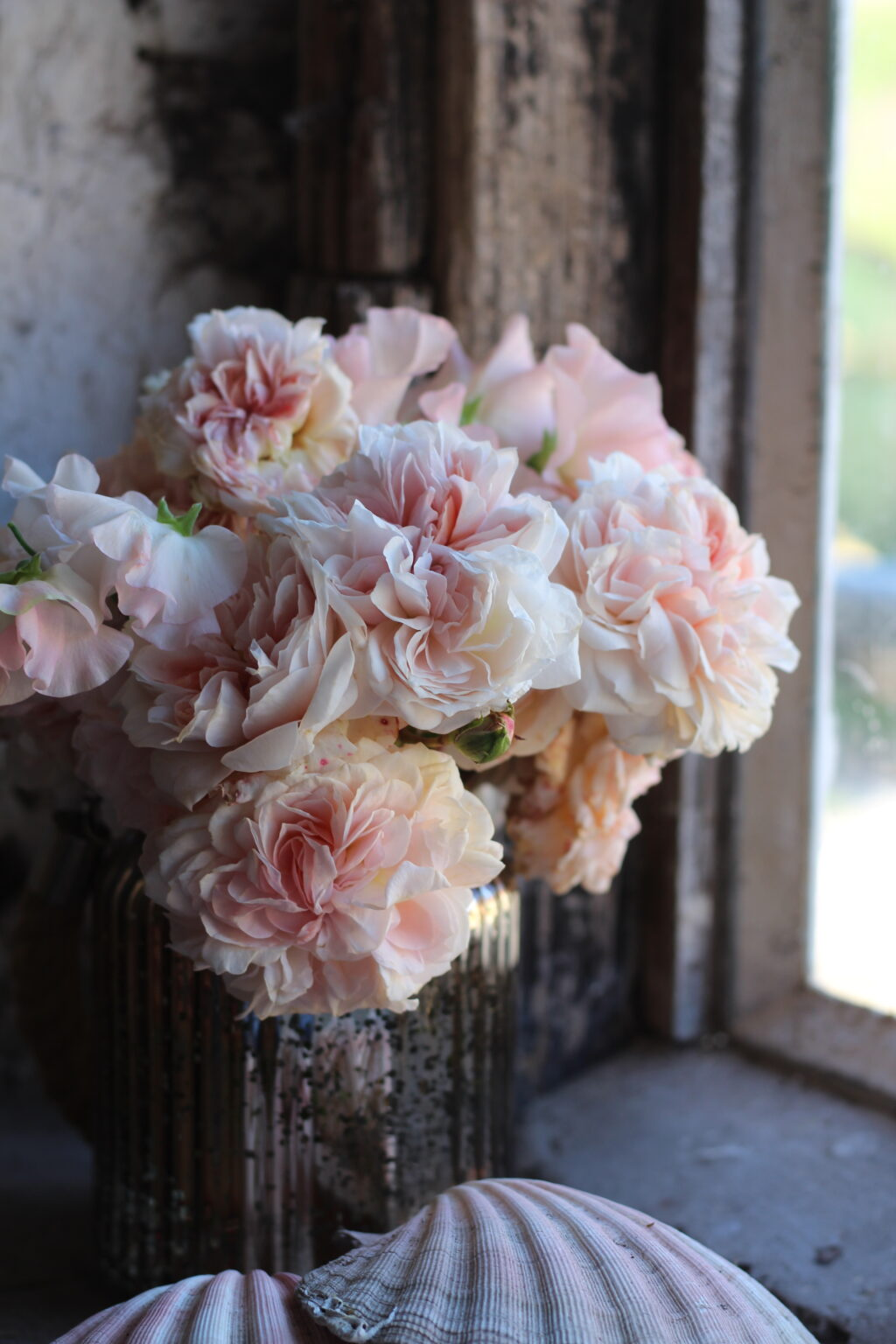 Pastel garden roses in an antiqued silver vase by Wildly Beautiful Flowers.