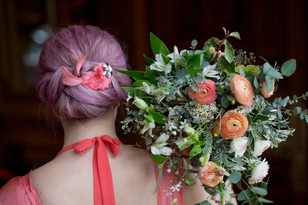 Bridesmaid holding a bouquet with coral ranunculus and alstroemeria by Wildly Beautiful Flowerers.