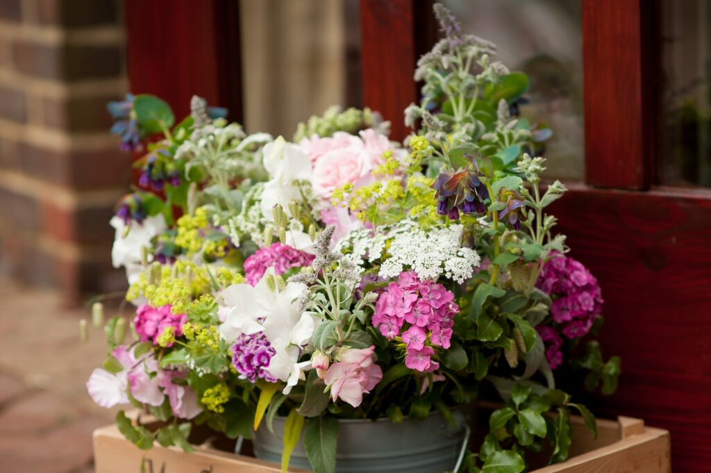 A wildflower style wedding flower arrangement by Woodchurch Cottage Flowers features the best of the late spring cut flower patch: perfumed sweet williams, sweet peas, garden roses, frothy Queen Anne's lace, sultry blue purple honey wort and the fresh lime green of lady's mantle.