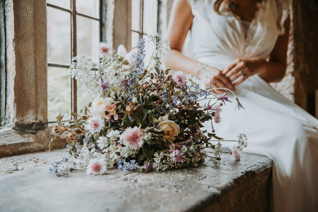 A wildflower style bride's bouquet rests on a windowsill with the summer flowers catching the light as the bride sits nearby. Yewbarrow Farm Flowers.