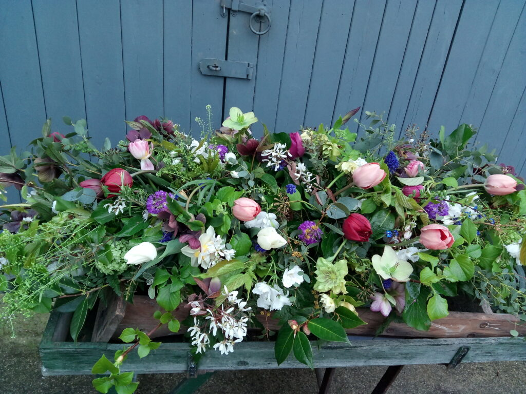 A colourful spring casket spray by the Yorkshire Dales Flower Company.