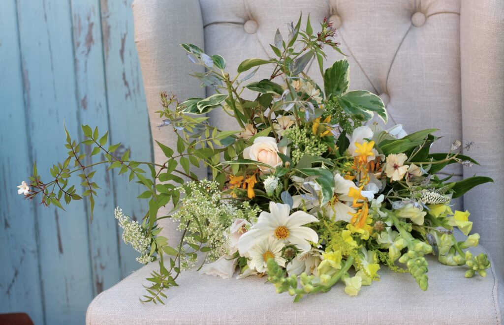 A leafy summer wedding bouquet with jasmine trails, variegated ivy leaves and summer flowers in yellows and whites. Photo: Tuckshop Flowers