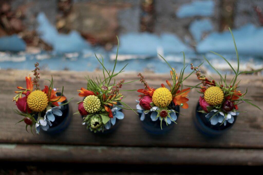 Late summer wedding buttonholes with yellow balls of craspedia, blue tweedier and bright pops of Crocosmia by Tuckshop Flowers, Birmingham.