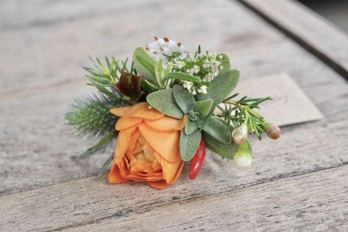 A spring buttonhole with sage and rosemary and chilli with an orange ranunculus for a keen cook
