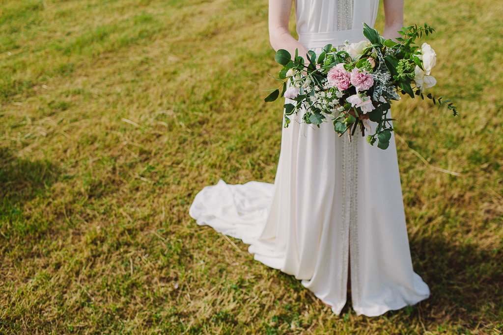 Wild escaping rose bouquet held by a festival wedding bride in a Worcestershire field! Tuckshop Flowers. Photo Sara Lemon