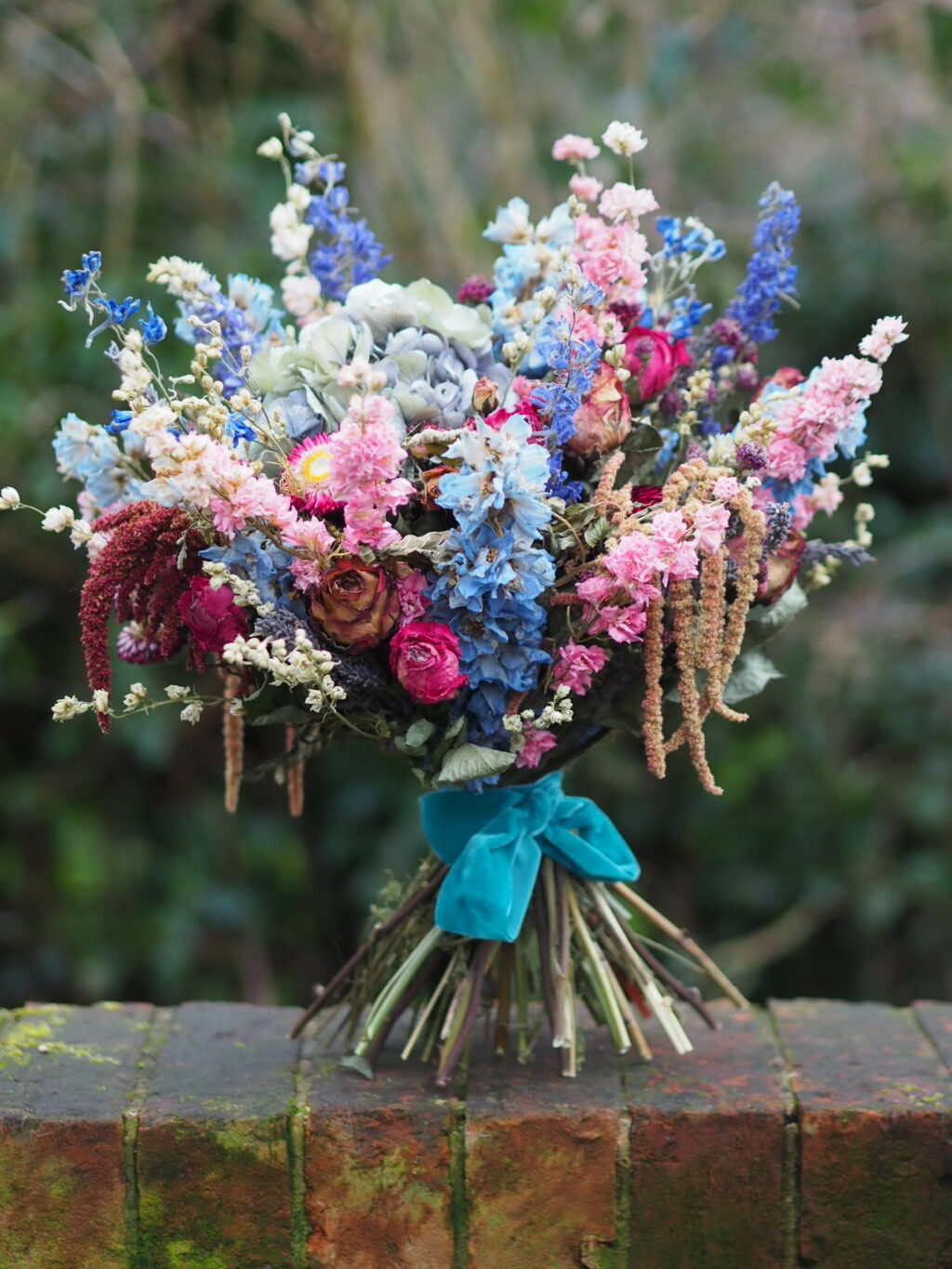 A beautiful bouquet of dried flowers tied with a turquoise ribbon by Flowers by the Bridge