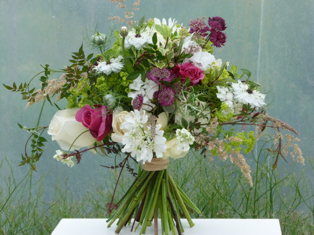 A beautiful early summer wedding bouquet with pops of pink amongst white flowers by The Sussex Cutting Garden