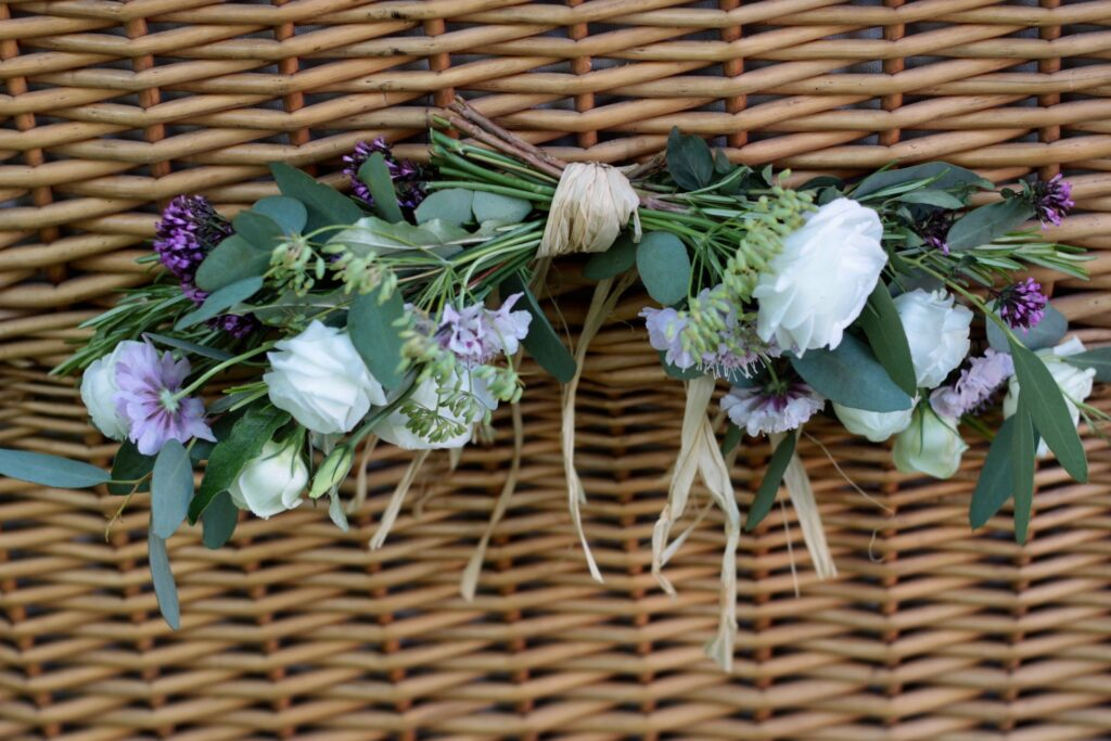 A small swag for a funeral attached to a wicker coffin. Tuckshop Flowers