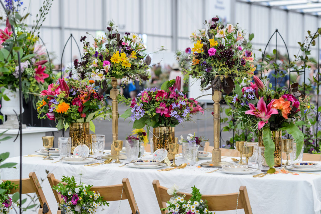 A celebration table filled with gold stands of wild, bright flowers at BBC Gardeners World Live. Flowers adorn the chair backs ready for the party. Photo: Jason Ingram.