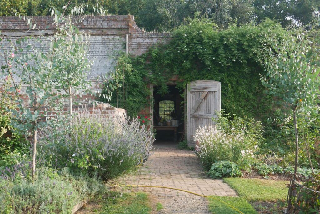 The old gardener's bothy at Stokesay Flowers is framed by foliage at the end of a path.