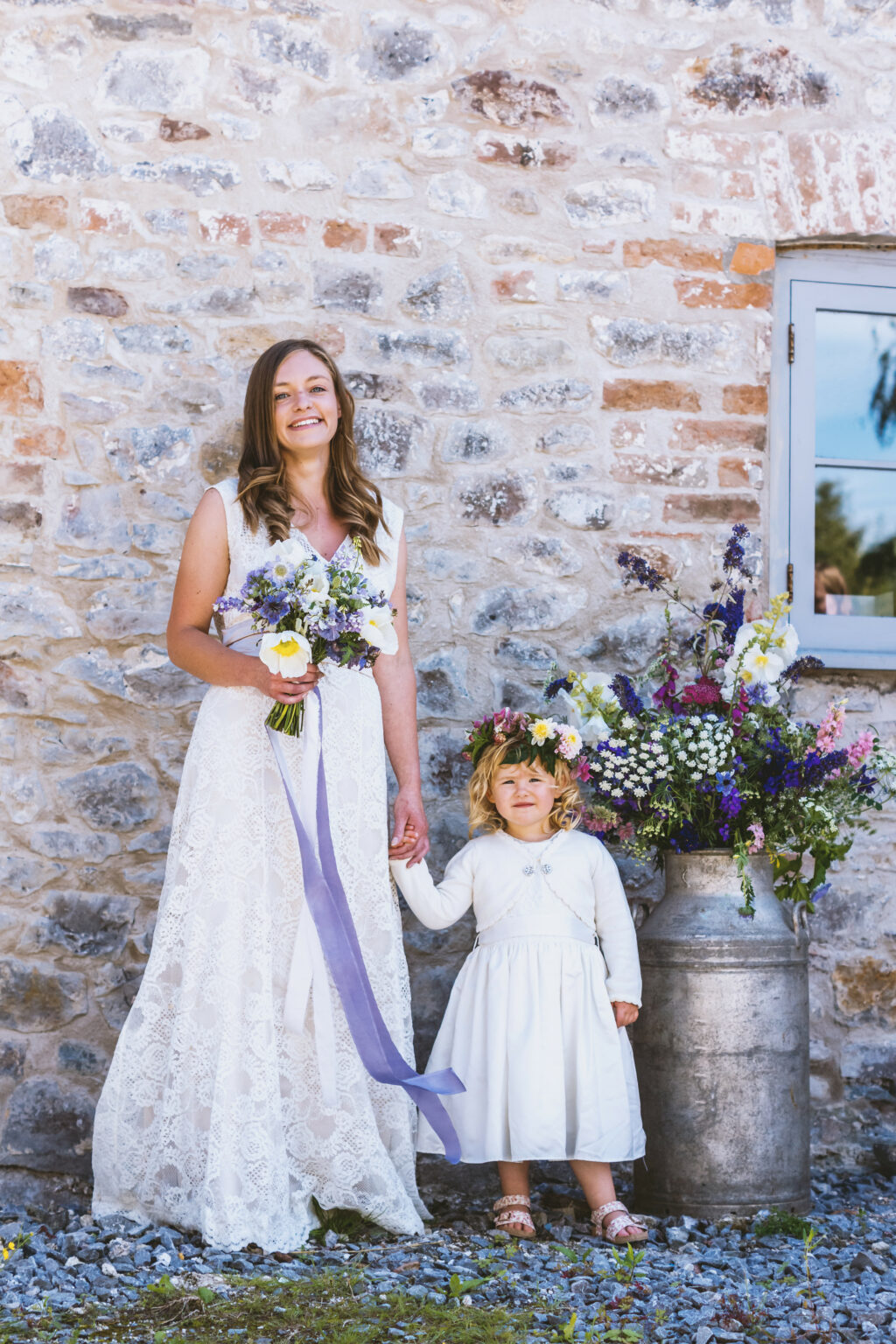 A bride and flower girl with British grown wedding flowers by The Floral Potager stand smiling against a rustic brick wall