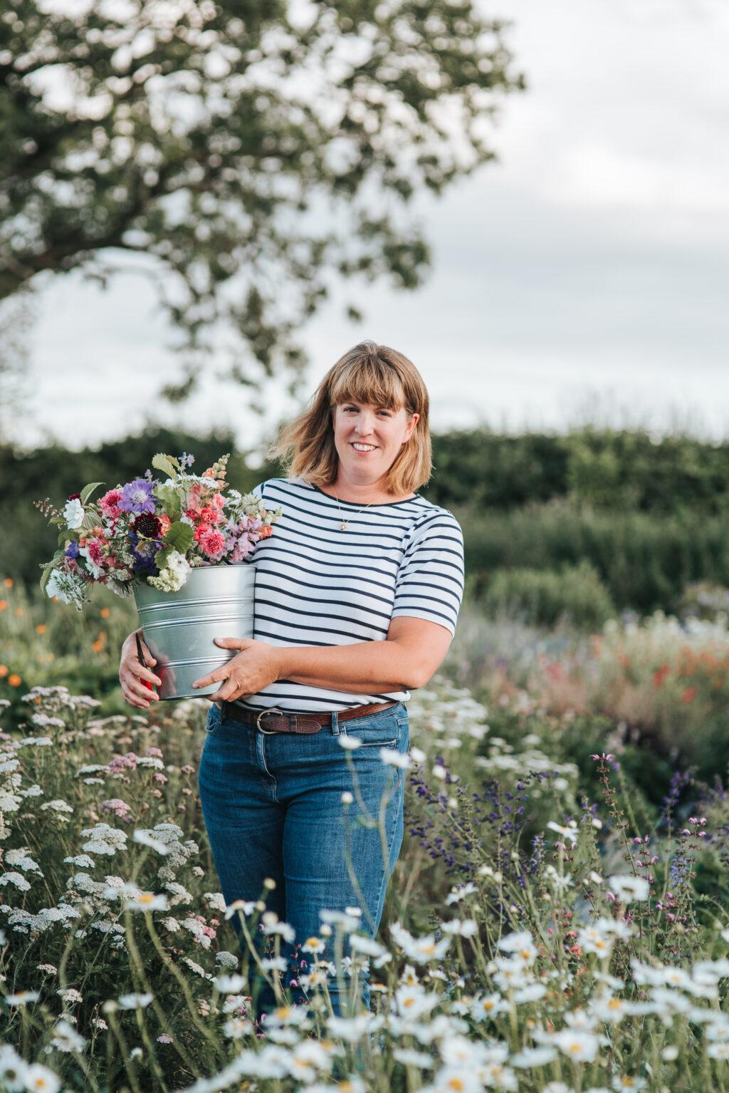 Caroline Onions of Wysall Flower Farm with a bucket of freshly picked flowers in her flower field