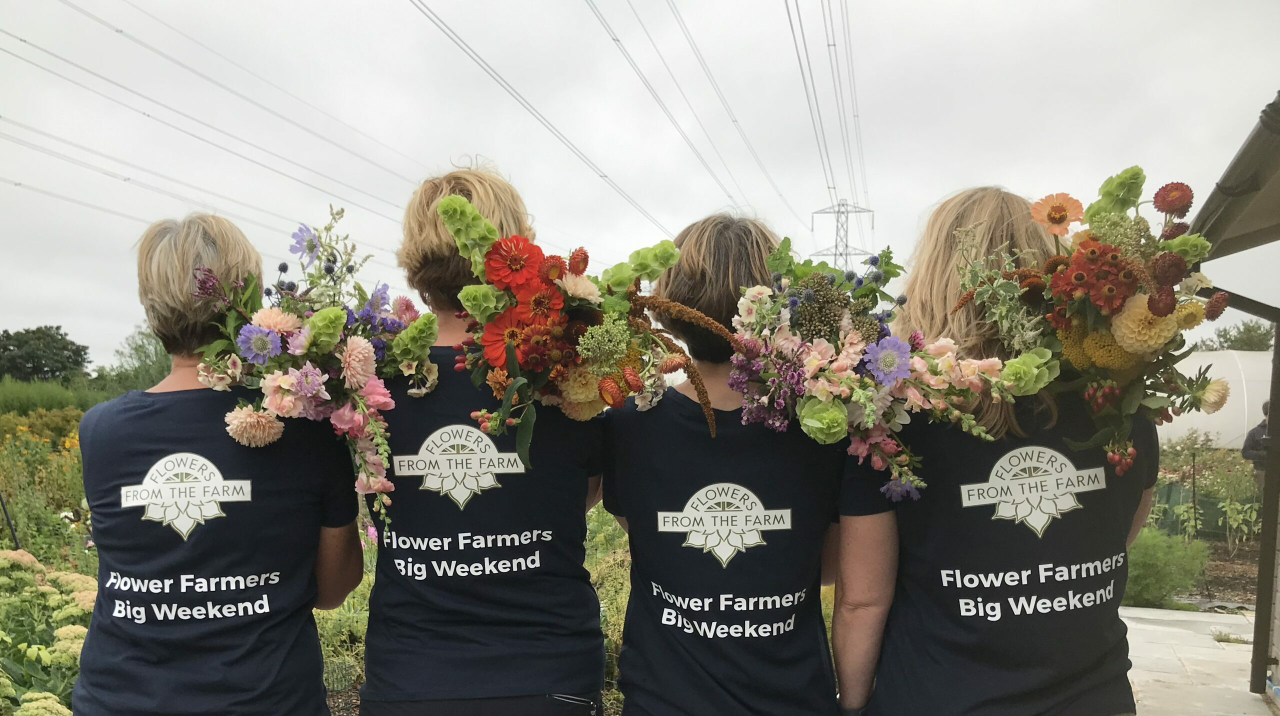 The team at Organic Blooms near Bristol with bundles of flowers on their shoulders ready for the Flower Farmers Big Weekend