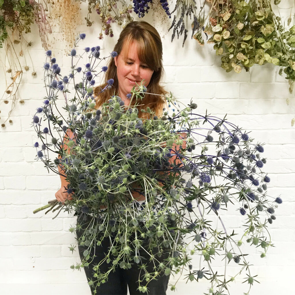 Sacha of the Floral Potager holds a huge bunch of silvery blue eryngiums in her workshop