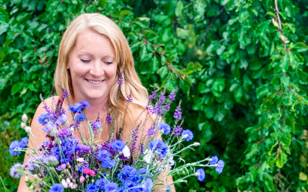 Catherine of Elworthy Flowers holds a bright bunch of locally grown cornflowers to celebrate British Flowers Week June 2021