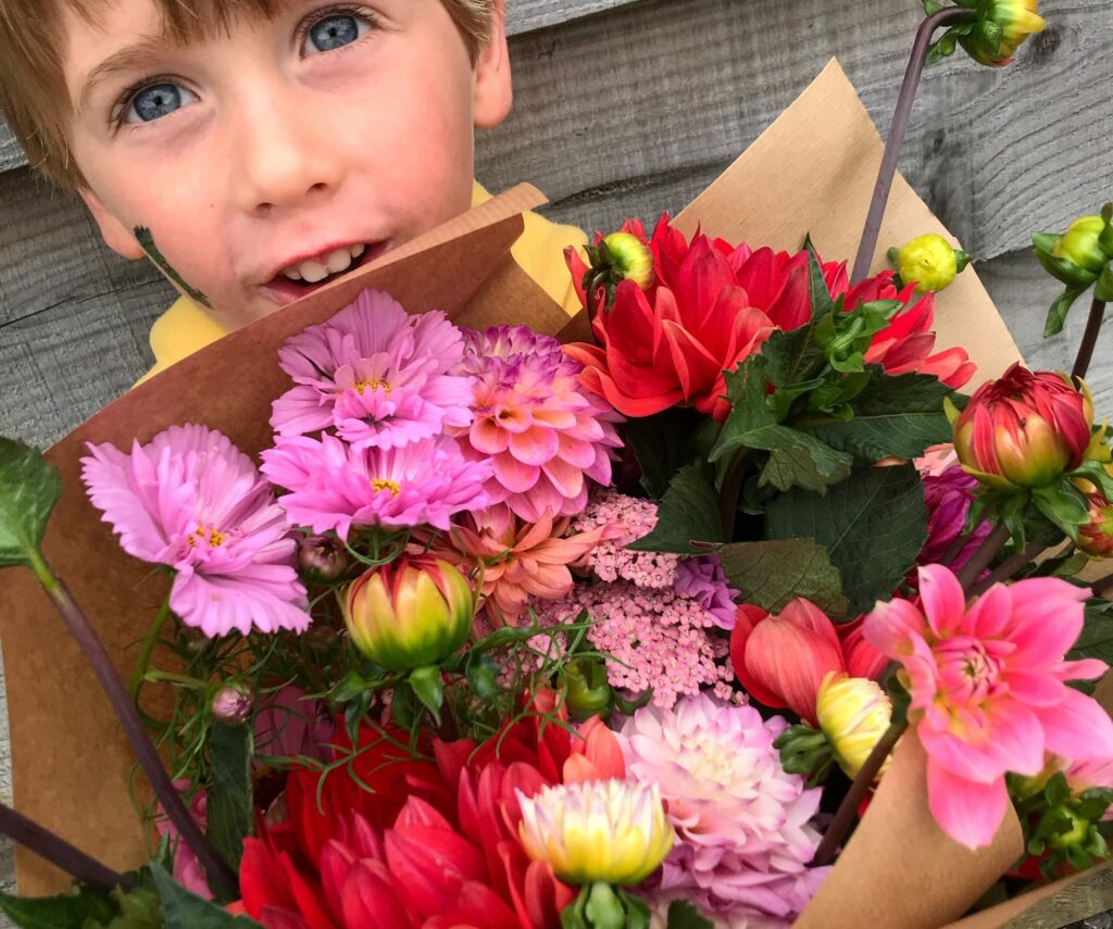 Child with arms full of pick your own flowers at Howe Farm Flowers