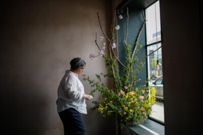 Rachel of Hedgerow adds the finishing touches to her wild window display for British Flowers Week in Edinburgn. Photo: Solen Photography