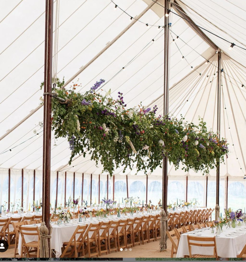 Moat Farm Flowers created this wonderful hanging installation above wedding trestle tables for in a marquee. The tables are filled with a botanical runner of small flowers in tiny containers.