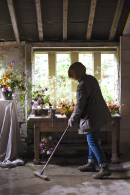 Sarah of Simply By Arrangement sweeps up after arranging flowers in her Yorkshire window for British Flowers week 2021