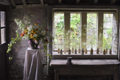 Simply By Arrangement's delicate window display consist of a parade of local British flowers in tiny vessels in mulllioned window, with a large tumbling arrangement on a linen covered plinth.