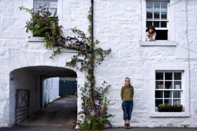 An installation of flowers climbs up the exterior wall at Tomnah'a Flowers, Scotland whilst the florists who created it lean out of windows and against the wall.