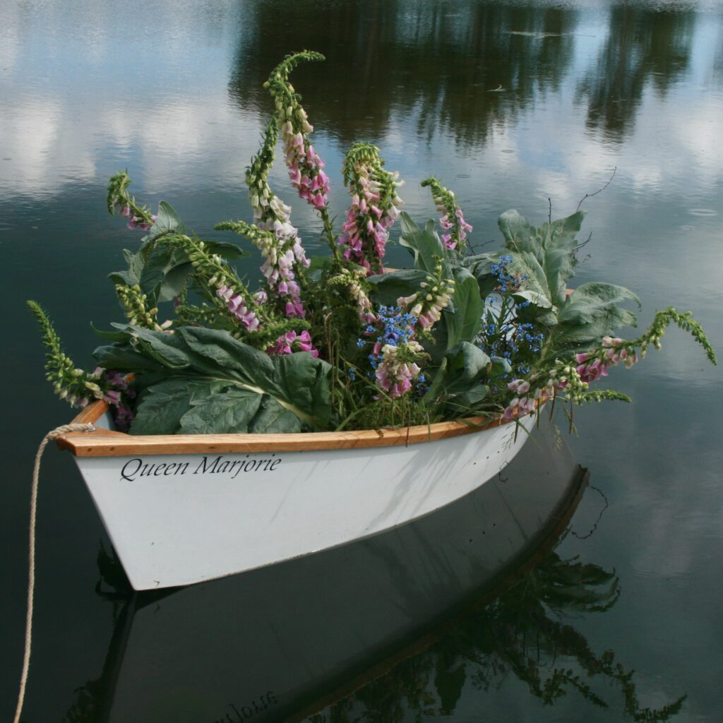 Millpond Flower Farm uses its mill pond to model a crop of its freshly picked locally grown flowers as they fill a rowing boat on the water.