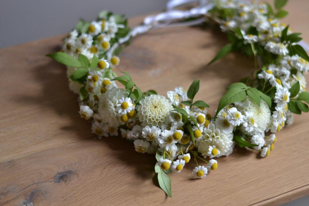 A summer flower crown of feverfew, white dahlias and jasmine foliage.
