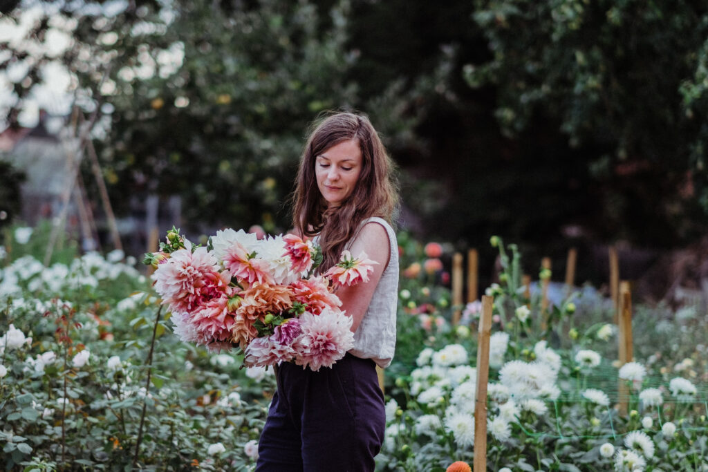 Rebekah holding an armful of dahlias at Elder and Wild