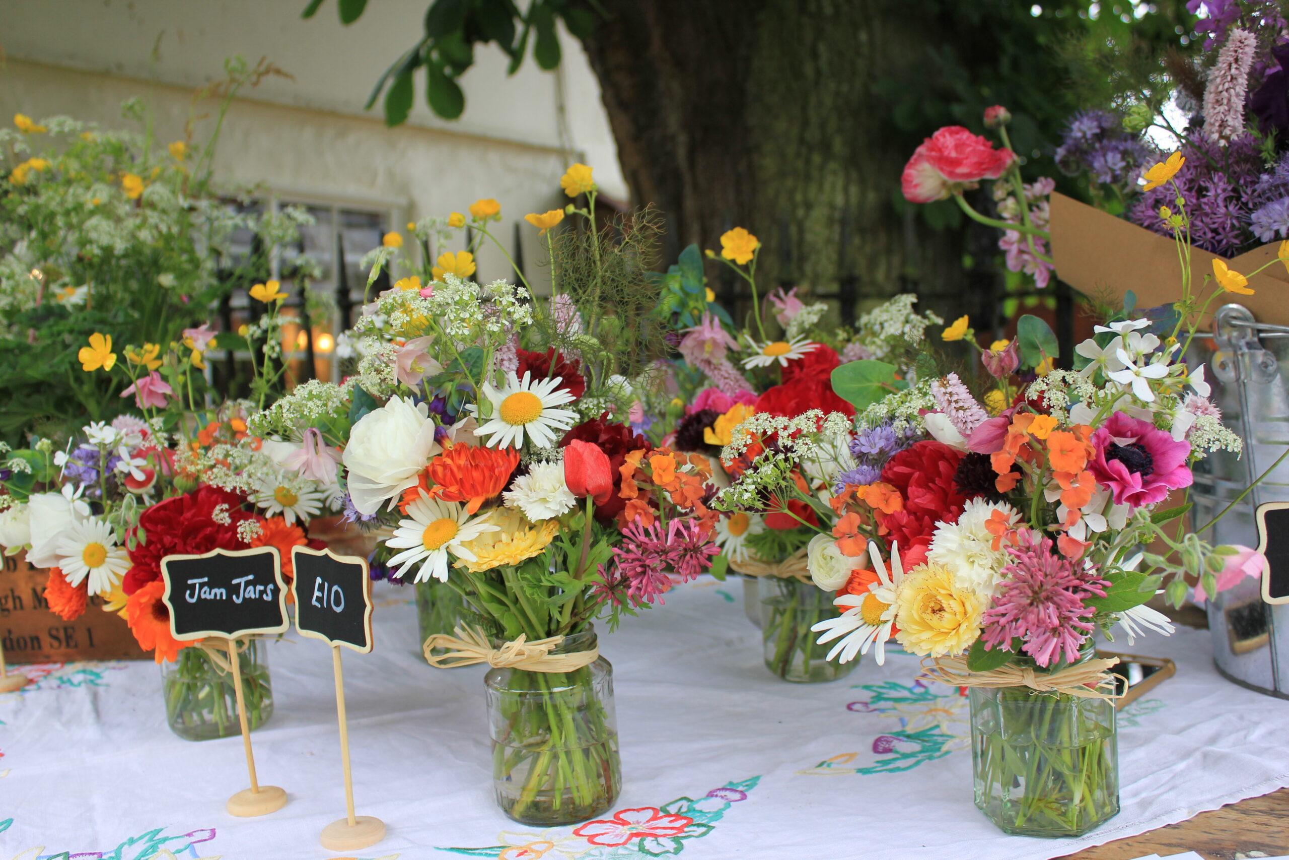 Jam jars of seasonal British flowers being sold at market